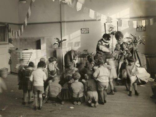 St. Nicolaasfeest op school, in de klas. St. Nicolaas en Zwarte Piet. Piet heeft net gestrooid, de kinderen rapen de pepernoten op.