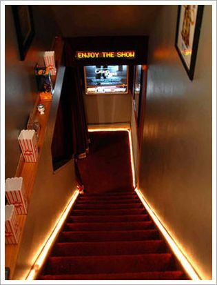 "steps down to a home theater are lined with concessions, carpeted thematically, and lit.  I like the ""Enjoy The Show"" sign, too."
