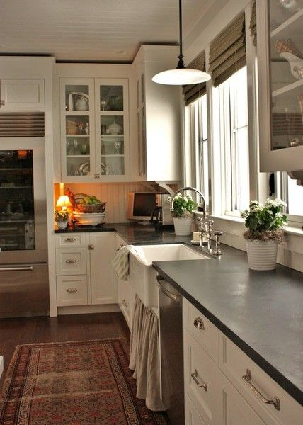 Classic kitchen look with bead board ceiling and backsplash, flush inset doors in cupboards painted cream, what appears to be a soapstone counter, wood floors, and an oriental carpet.