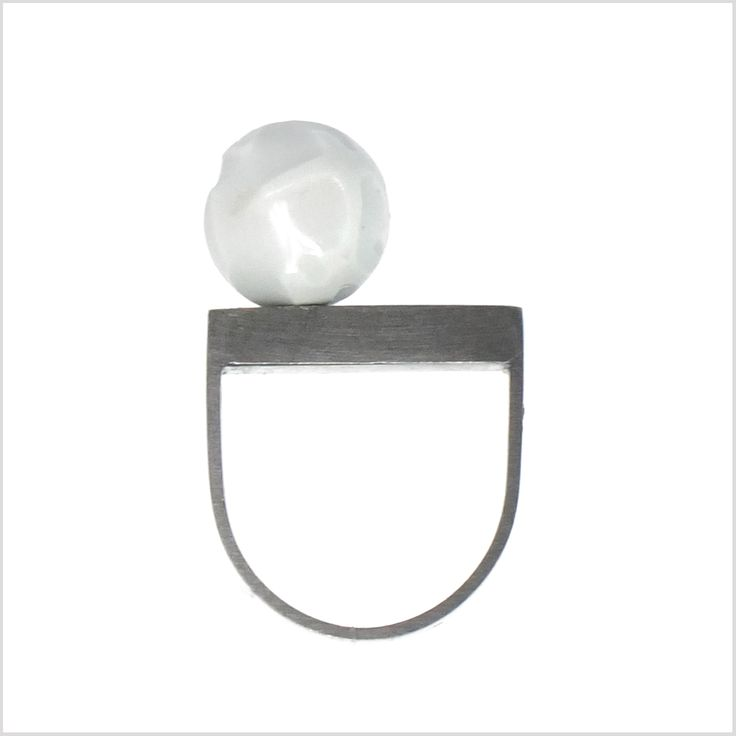 Oxydized silver ring with porcelain ball and silver from SU-MIN collection. The white porcelain ball was designed by famous polish artist Bogdan Kosak. Every single piece is unique. The irregular lines are artist interpretation of a long grass in his home village SUMIN.