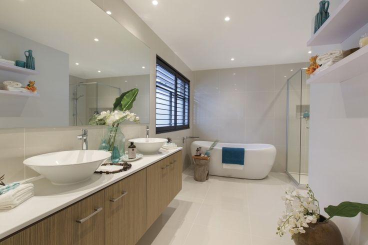 This stunning bathroom emits the relaxing ambiance of the Maldives through its soft timbers and clean white lines in the benchtops and tiling. Pops of sea blue in fabrics and vases help create this perfect getaway.