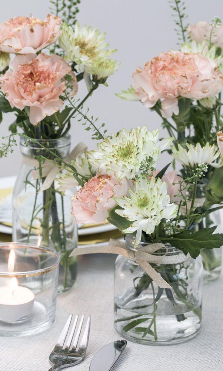Et par små buketter med tulipaner eller roser og grene, der går igen ved borddækningen