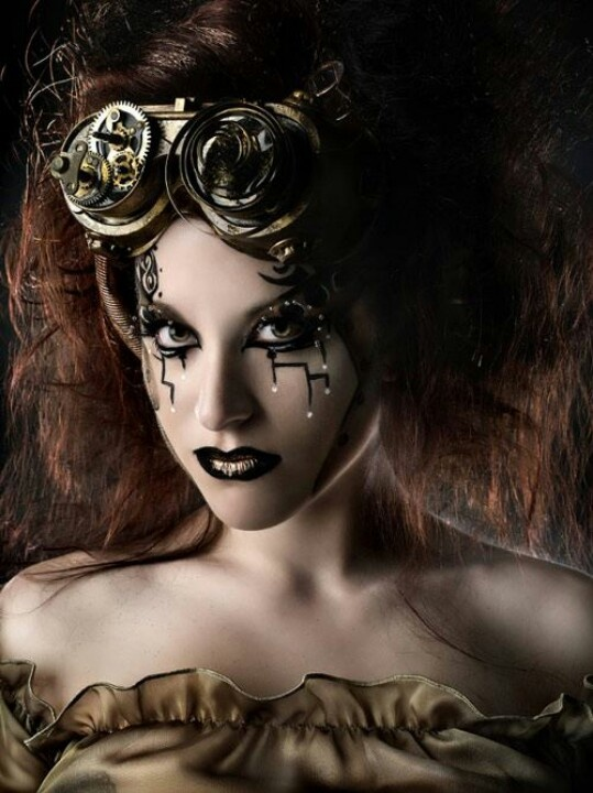 Steampunk fashion beauty shot showing futuristic make-up details commplimenting the gear work head piece.