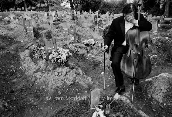 Sarajevo - A City Under Siege. Photo by Tom Stoddart. Cellist Vedran Smalovic breaks down in tears after playing a requiem to a dead friend at Hero's Cemetery, where Bosnian fighters were buried during the siege of Sarajevo, 1992