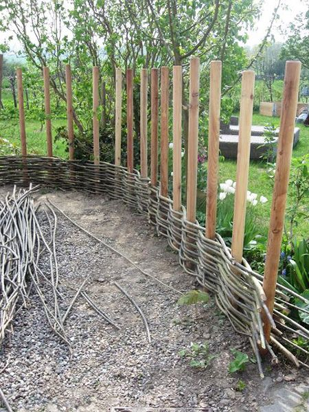 """Okay, this idea would only work if you have access to long, thin branches. And not any branch will do. They need to be """"green"""". That means that there are fairly fresh and easily bent. But if you can get them, use the branches to weave a basket style fence like this. Super cool idea!"""