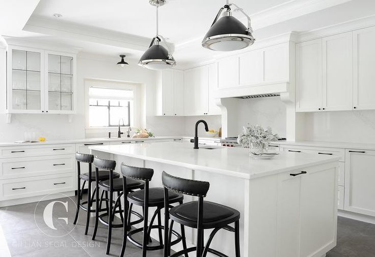 Two tone black and white kitchen boasts two black industrial pendants hung from a tray ceiling above a white island topped with a white quartz countertop seating four black leather counter stools facing an island prep sink paired with an oil rubbed bronze gooseneck faucet.