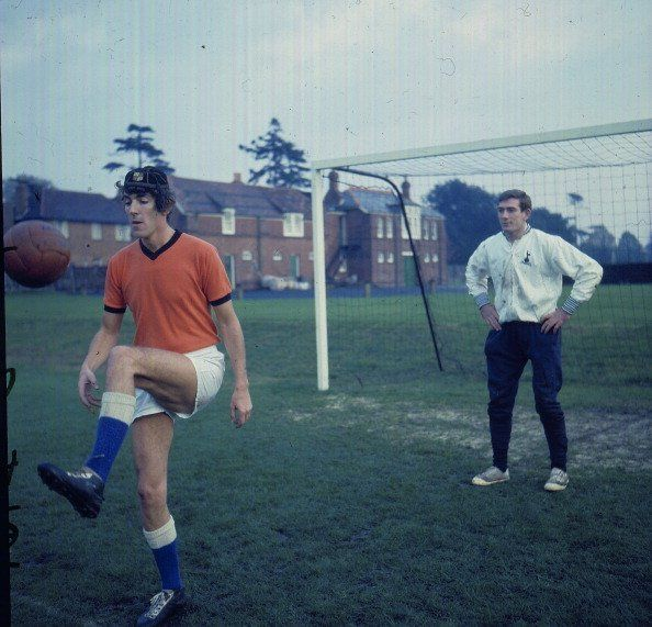 Tottenham Hotspur's Pat Jennings looks on while comedian Peter Cook shows off his keepy uppy skills