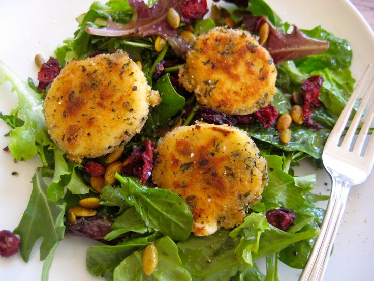 A bed of arugula topped with baked goat cheese.