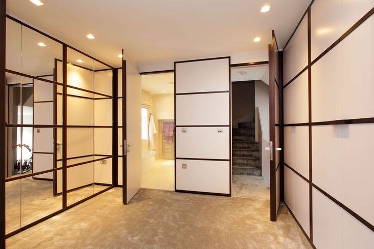 Dressing room featuring concealed doors open to the hallway by Andrew Manning Furniture