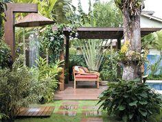 Ao fundo, aberta como um leque, está a árvore-doviajante. No solo, repare nas paginações dos minideques de itaúba. Eles levam os moradores aos pontosde atração, como o original chuveirão. Feito com uma espécie de chapéu artesanal (Bambu Decorações), ele dá um toque balinês ao jardim.
