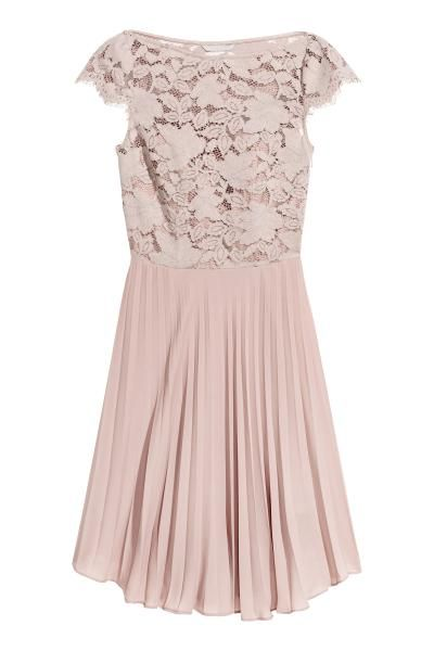 Een knielange jurk van geweven kwaliteit met een kanten lijfje met een boothals en kapmouwtjes. De jurk heeft een naad in de taille, een geplisseerde rok en