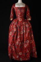 1780- 1785 Japon, robe à l'Anglaise van sits, rood fond met grote veelkleurige bloemen, lijf met vestpanden, aangeplooide rok, mouwen met geplooid elleboogstuk, vierkante halslijn