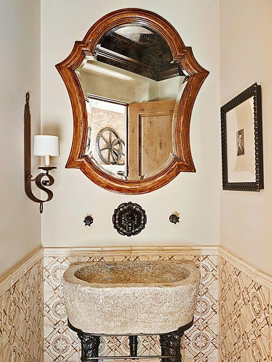 Mediterranean bathrooms and powder rooms should feel distinctive and collected. Every item in this powder room -- the carved sink set atop turned legs, the wall-mount faucet, the lovely looking glass, the tiled wainscoting -- contributes a singular patina or pattern to the design.
