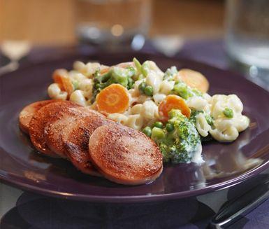 Stuva makaronerna i mjölk och muskot så att de får en riktigt krämig konsistens innan du blandar i fräscha grönsaker som broccoli, sockerärtor och morot. Servera med falukorv som stekts eller grillats till de fått en krispig yta.