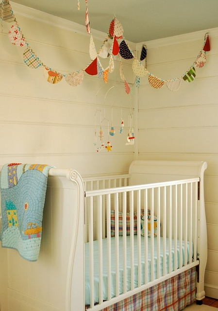 Lovely eclectic space. The draping banners look a bit like a pointed castle roof over the crib. Better than a mobile.