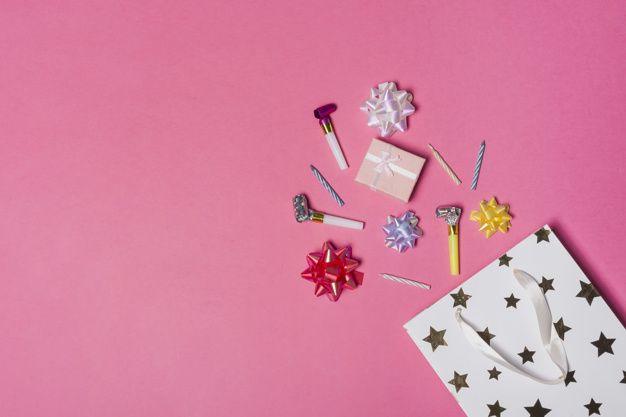 Derramando colorido arco de satén; caja de regalo; sopladores de fiesta y velas…