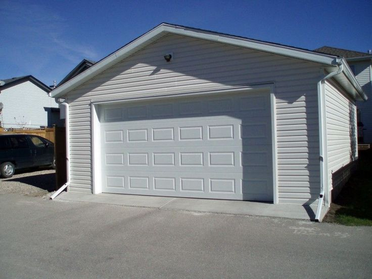 Awesome Prefab Garages Near Clear Wall Made From Concrete Along With Clear Wooden Garage Door With Several Blocks Ornament