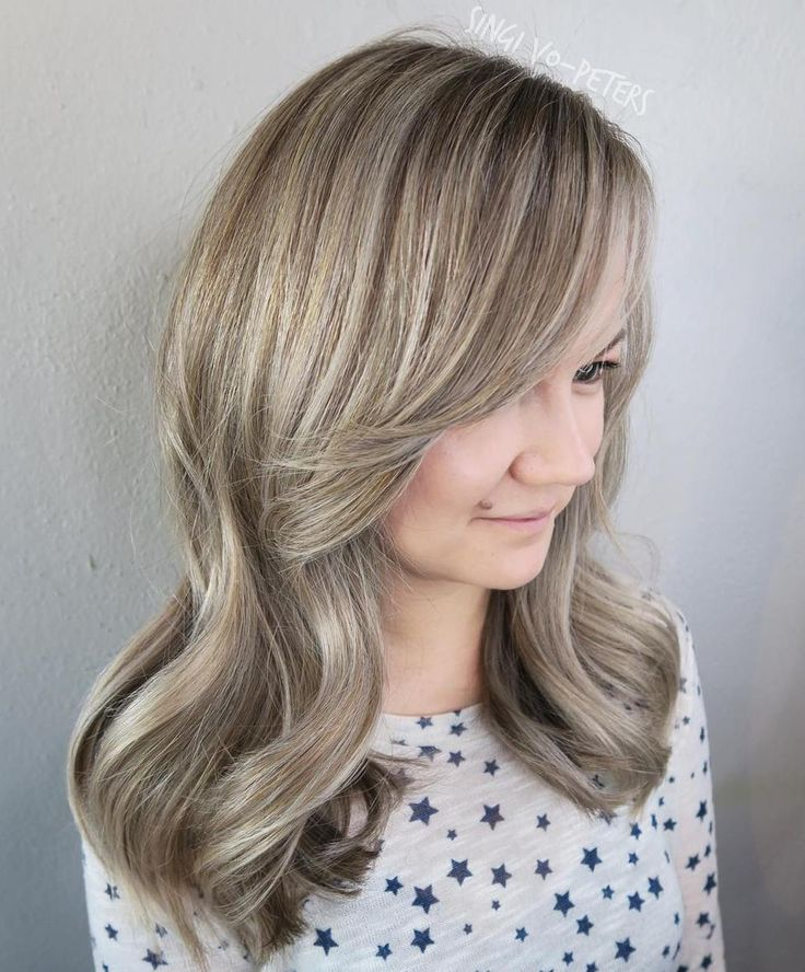 Silvery pieces woven into her ash brown/blonde base give her hair some radiant shimmer. The cool-toned lowlights make this style dimensional.