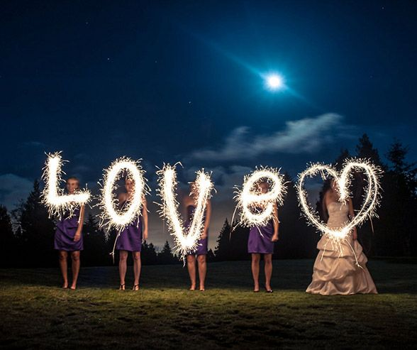 """Under the moonlight, a bride and her bridesmaids spell """"love"""" to create a fantastic sparkler photograph."""