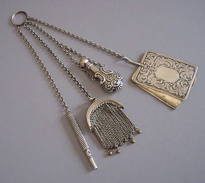 Chatelaine ring with hanging mesh coin purse.   Chatelaine is a decorative belt hook or clasp worn at the waist with a series of chains suspended from it.