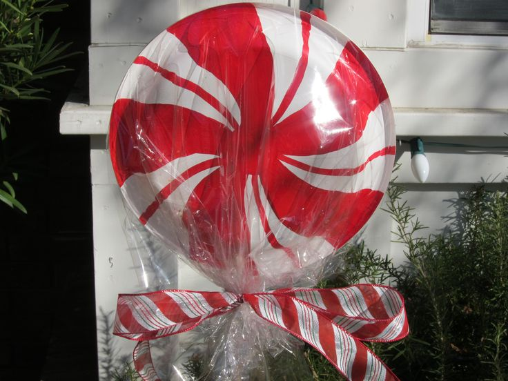 Paper plates wrapped in cellophane on a dowel stick for the yard art,     I did not paint plates, I bought a pkg similar and hot glued them on a dowel stick.  I the glued a regular heavy (chinet) paper plate to the back to cover the stick.  Wrapped in cellophane and tied a bow.