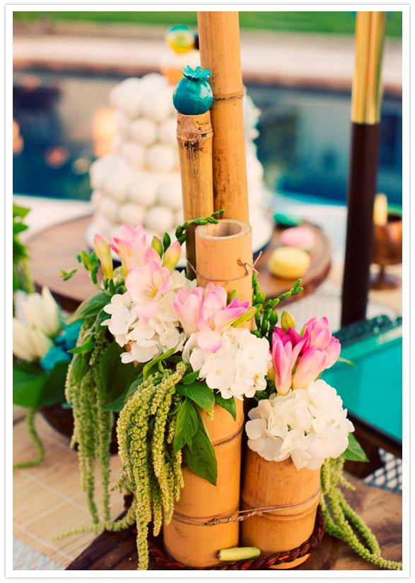 bamboo vase centerpiece- I'd like it better with bird of paradise or more Hawaiian flowers