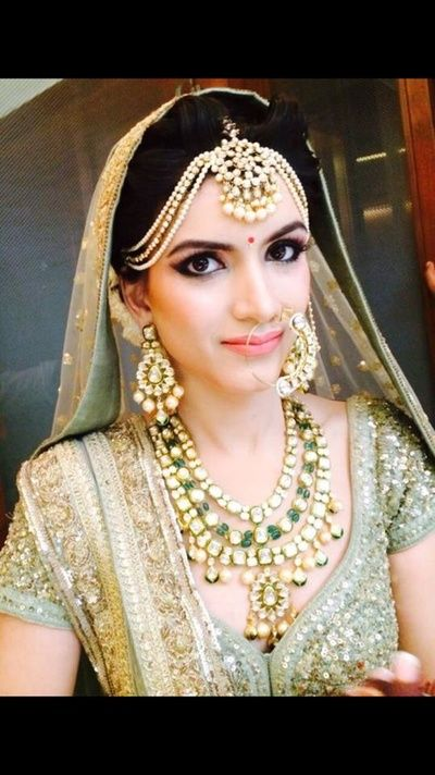 three strings maatha patti , big maang tikka  with pearl drops , three strings polki necklace m  heavy jewellery , bridal jewellery , rich and luxurious , high class , royal and magnificent jewellery , mint and gold lehenga , beautiful bride