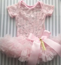 What an adorable pink bodysuit tutu dress! Perfect for those birthday pictures! The dress is made with the softest chiffon ruffles and pretty lace bodysuit.... The bow can be customized in any color!  ~snap closure for easy diaper change  ~pairs great with Pink and gold birthday headband  ~ready to ship within 1-2 business days!  days!  {{Comes in 5 sizes}} Measurements from over shoulder to snaps:  0-3 months: 14  3-6 months: 15  6-9 months: 17  9-12 months: 18  12-18 months: 19 **a…
