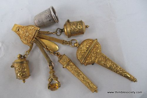 Child`s chatelaine  18th century ormoulu child's chatelaine with silver thimble to illustrate scale. A waist belt clip, with pendants as following, thimble cases, scissor case, needle case, letter seal with citrine. No tools inside, but this is normal as tools to fit would have been purchased later. Probably given to a young girl, more as a fashion item than to be used.Children's chatelaines are very rare as they were expensive even in the time of creation.  4ins  £750