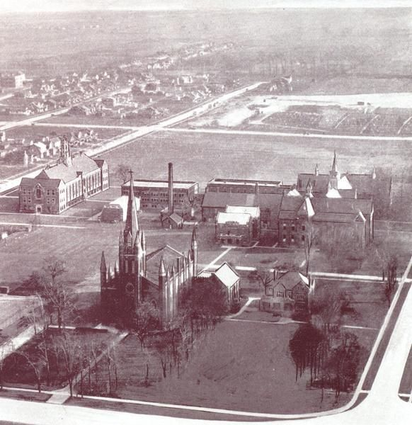 """""""Seen from the Bridge Tower""""; Dillon Hall (aka Arts Building, or, Classroom Building), built in 1927/1928, is on the left, with Patricia Road in front; Assumption Church (completed in 1845) is in the foreground, with London Street (now University Avenue) in front; Assumption Parish Residence is to the west of the church; Assumption College is mid-ground, with Huron Church Road in front; Wyandotte Street runs east-west across the top of the photograph. Windsor,Ontario"""