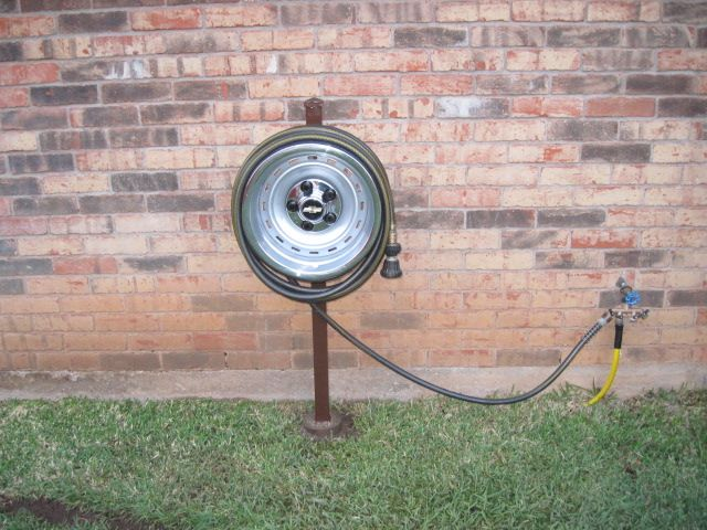 """bent 15"""" X 8"""" chevy truck rallye rim no good for use on vehicle, perfect for garden hose hanger. Made by my husband!"""