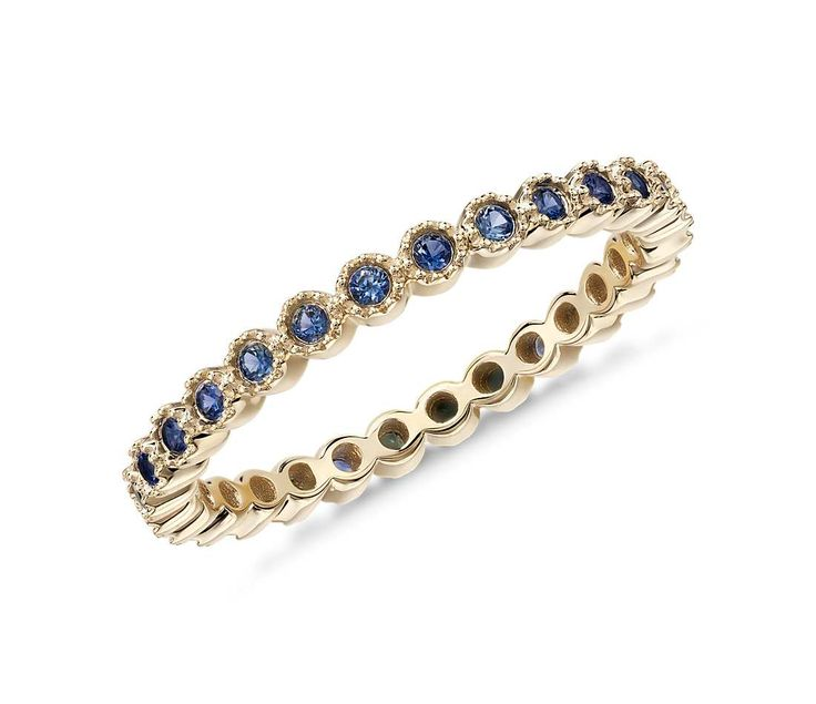 This stackable eternity ring features blue sapphire and round brilliant diamonds crafted in a petite design of 14k yellow gold.