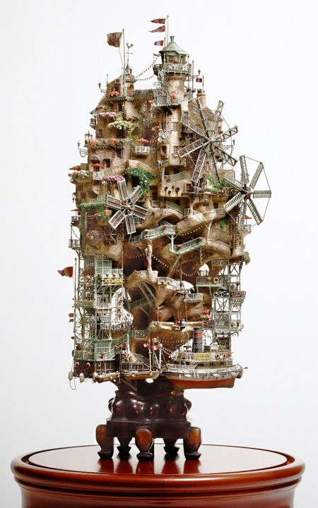 Japanese artist Takanori Aiba builds tiny houses on top of small rocks and miniature trees.