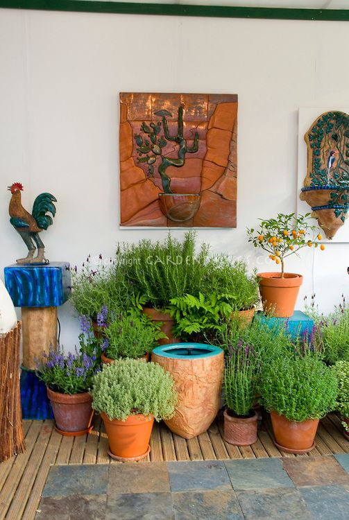 Pretty variety of pots and container garden of herbs for Garden decking ornaments