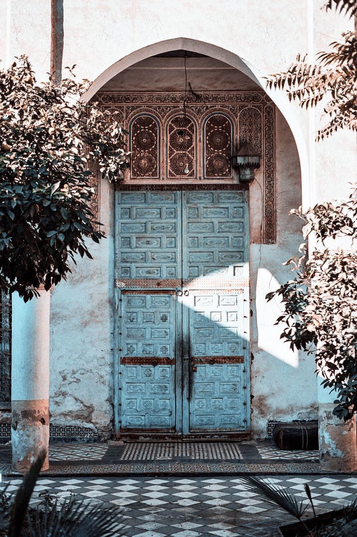 There is something achingly beautiful about the combination of ancient doors, their colour faded by time, tiles that subtly echo their colour, flowering plants and the addition of soft diffused light. If ever there was a combination of elements that called you to be there - this is it.