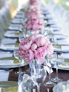Simple floral arrangement made with peonies or your favorite flower. These flowers were placed in glass vases and lined symmetrically in the middle of the table.  A simple yet chic place setting laid on opposite sides of the centerpiece and voila!