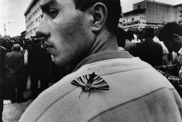 Turkey. 1990. Yozgat. Political meeting. Nikos Economopoulos. There seems to be an element of juxapostion in this image too, as the butterfly represtents freedom and beauty.