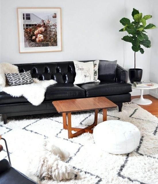 Ledersofa Kaffeetisch weiße Dekokissen Teppich Design