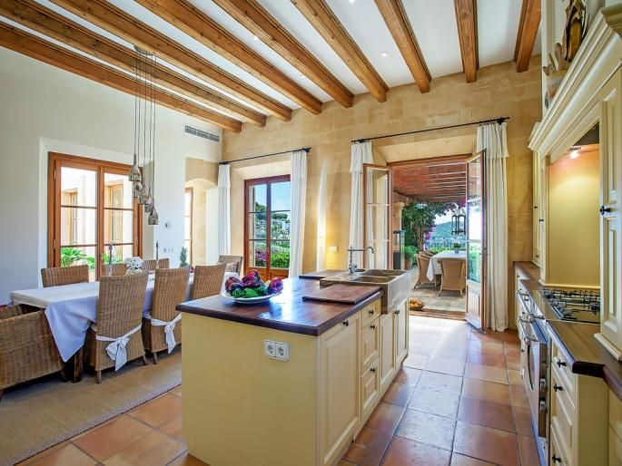 Open kitchen with island and adjacent dining area in Mediterranean style from Camp de Mar, Port Andratx, Mallorca.