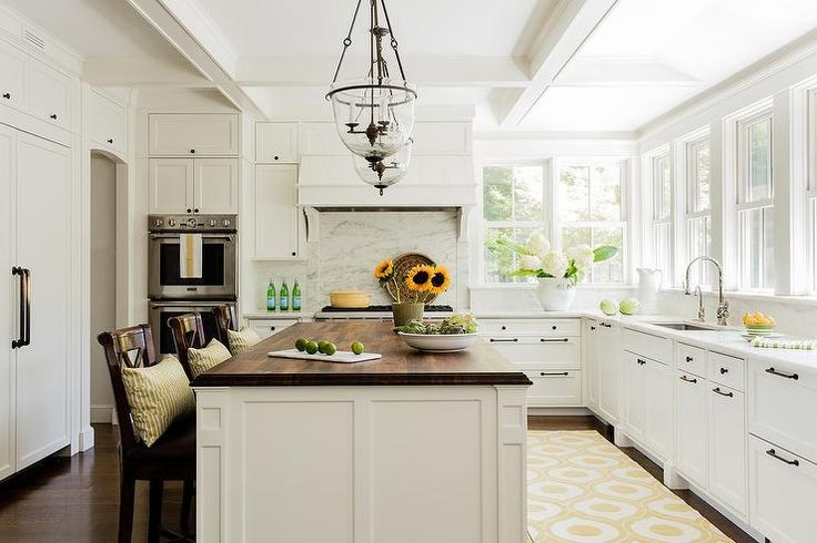 A pair of glass bell jar lanterns hang over a white kitchen island topped with walnut lined with wood counter stools accented with brown leather seats.