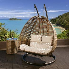 Dark brown rattan two person hanging chair with cream cushion covers.