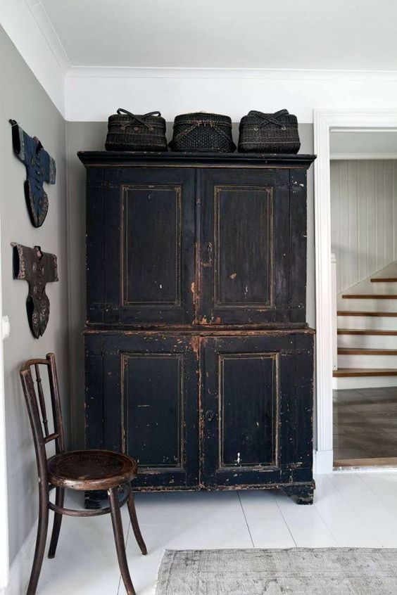 Armario rustico negro y una silla modernista de madera