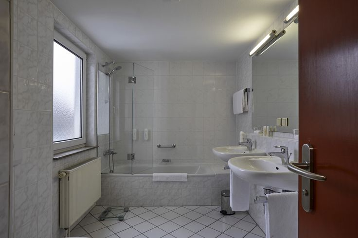 Ein großzügiges Badezimmer mit Badewanne und Dusche gehört auch zu den Annehmlichkeiten des H+ Hotel Darmstadt