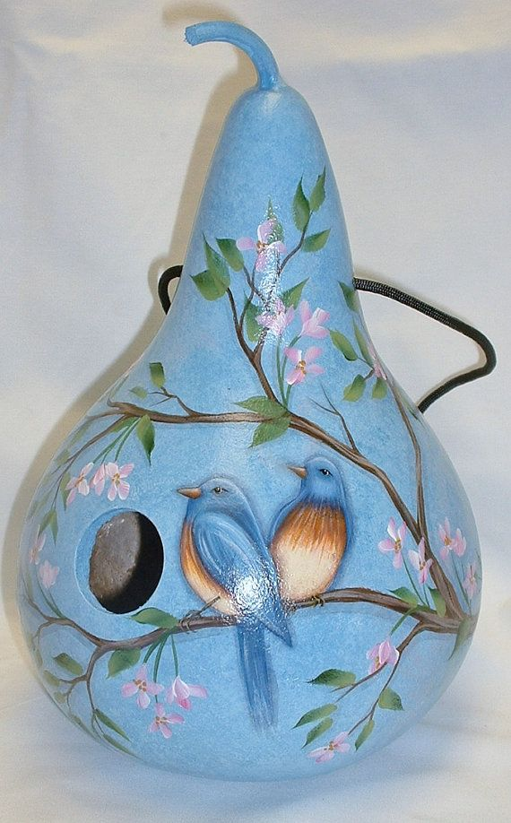 My blue bird and cherry blossom birdhouse is hand painted on a kettle gourd. It is 11 tall and 24 around. It hangs from a black nylon cord and has