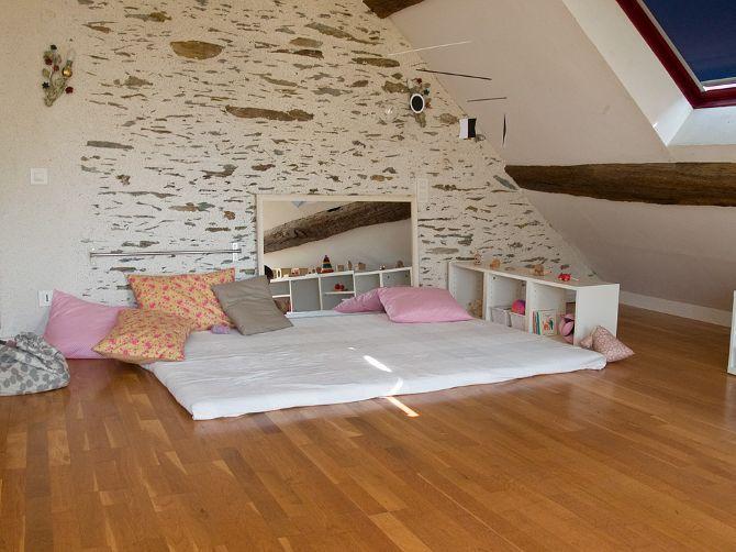 """Espace Nido avec lit au sol, mobile Munari, barre pour se lever, miroir, casier avec """"jouets"""" à portée de l'enfant, etc."""