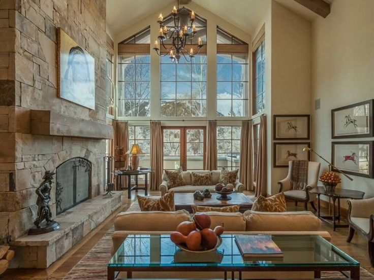 Elegant two story living room with rustic touches, including massive stone fireplace with natural wood beam mantle at left. Full height windows shaped to the vaulted ceiling illuminate a space filled with brown cushioned furniture holding patterned pillows over a hardwood floor.