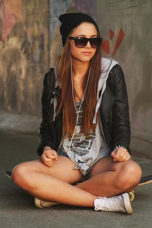 Leather jacket, skull graphic tee, shorts, and white Converse.