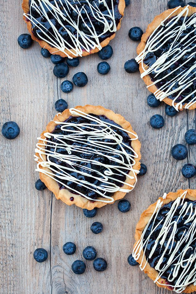 Buttery, crunchy tart shells filled with gooey, fresh blueberry filling and a white chocolate drizzle! | spachethespatula.com #recipe