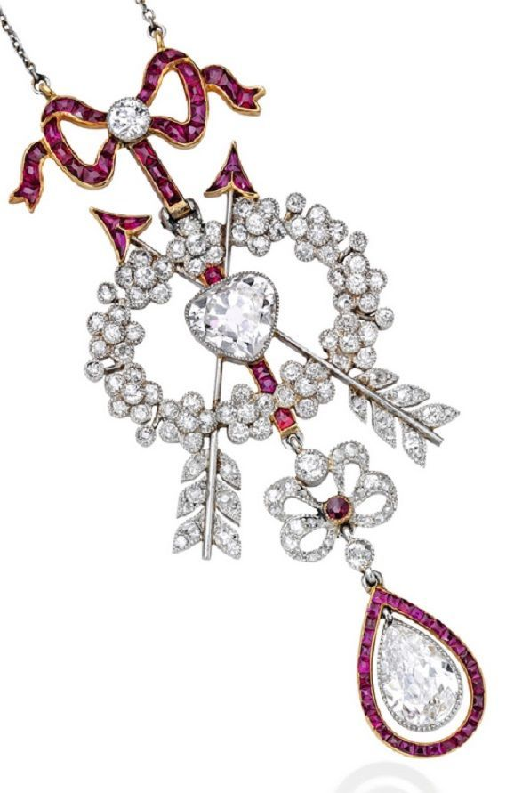 Cartier - A Belle Epoque Platinum, Gold, Diamond and Ruby Pendant-Necklace, Circa 1910. The floral wreath centring an antique heart-shaped diamond weighing approximately 1.00 carat, decorated with two intersecting arrows and two bow motifs, suporting an antique pear-shaped diamond weighing approximately 1.00 carat, set throughout with numerous small old European, single and rose-cut diamonds, accented by calibré-cut rubies, length 16½ inches, signed Cartier, numbered.