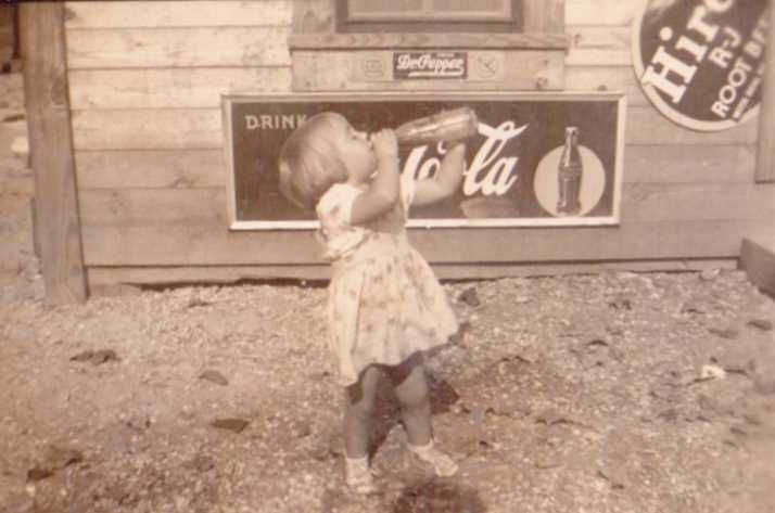 Pretty little girl (unidentified) drinking from a soda bottle in front of a north Louisiana country store. Probably taken in Winn Parish in the early 1940's.